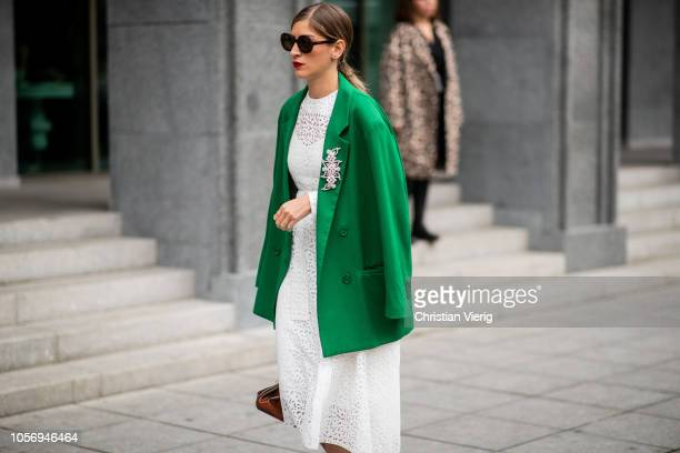 A guest is seen wearing white dress green blazer during MercedesBenz Tbilisi Fashion Week on November 3 2018 in Tbilisi Georgia