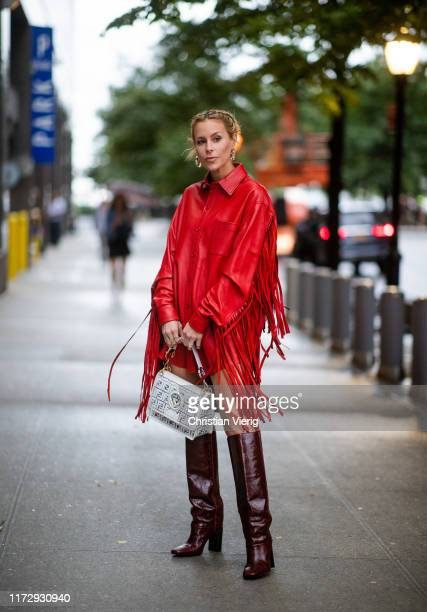 Guest is seen wearing white Fendi bag, bordeaux boots, red jacket with fringes outside Rag & Bone during New York Fashion Week on September 06, 2019...