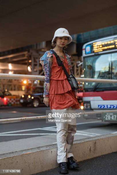A guest is seen wearing white Kangol bucket hat red/white/blue shirt orange dress black bag and white pants during the Amazon Fashion Week TOKYO 2019...