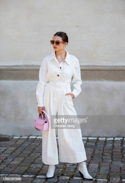 Guest is seen wearing white overall, pink bag outside Remain Birger Christensen during Copenhagen Fashion Week Spring/Summer 2021 on August 11, 2020...