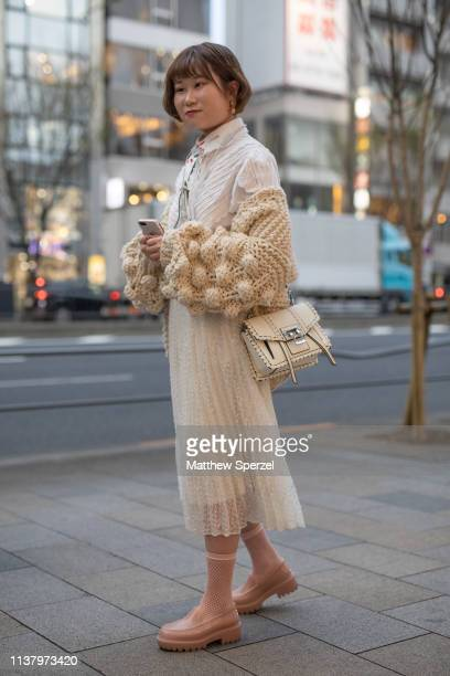 A guest is seen wearing white sheer dress with knit sweater and cream bag during the Amazon Fashion Week TOKYO 2019 A/W on March 23 2019 in Tokyo...
