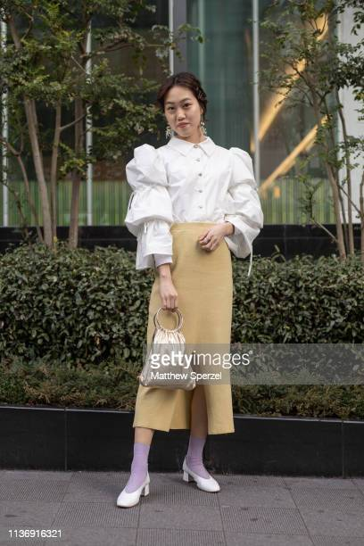 A guest is seen wearing white shirt yellow skirt gold metallic bag with white heels during the Amazon Fashion Week TOKYO 2019 A/W on March 19 2019 in...