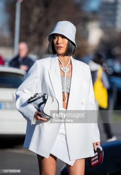 A guest is seen wearing white skirt blazer bucket hat cropped top bag Prada outside Prada during Milan Fashion Week Fall/Winter 20202021 on February...