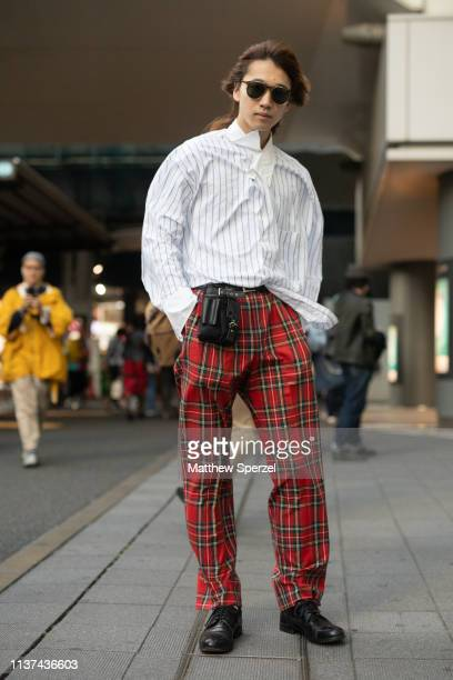 A guest is seen wearing white striped shirt red plaid pants utility pouch and black shoes during the Amazon Fashion Week TOKYO 2019 A/W on March 21...