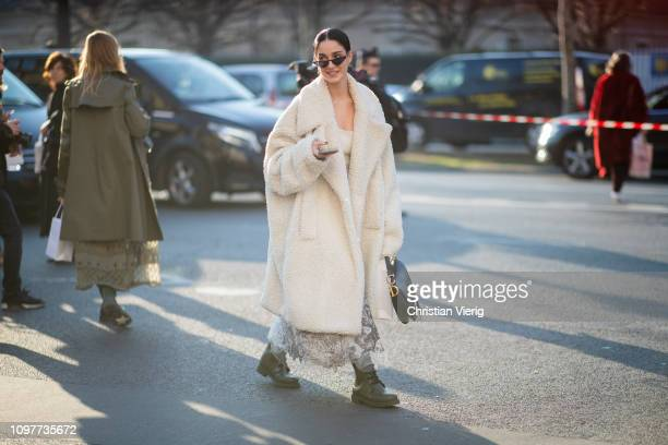 A guest is seen wearing white teddy coat outside Dior during Paris Fashion Week Haute Couture Spring Summer 2019 on January 21 2019 in Paris France