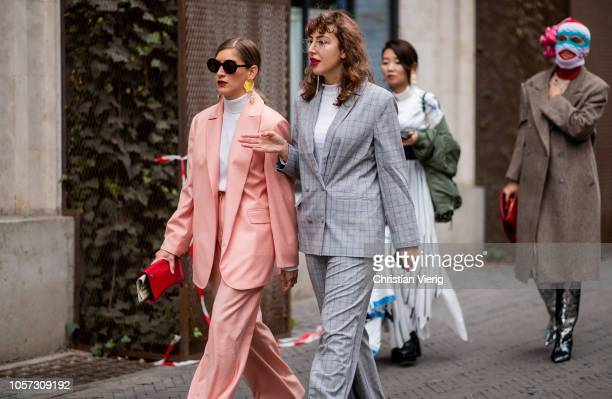 A guest is seen wearing white turtleneck pastel suit and a guest wearing grey suit during MercedesBenz Tbilisi Fashion Week on November 4 2018 in...