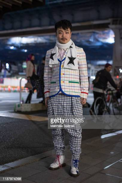 A guest is seen wearing white with colorful grid pattern coat blue checker shirt and pants white star design scarf during the Amazon Fashion Week...