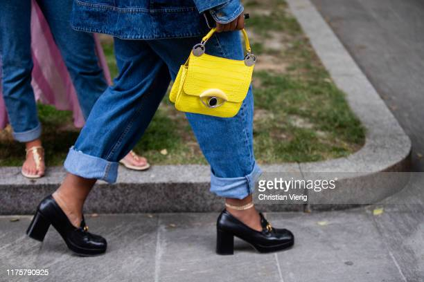 Guest is seen wearing yellow bag outside the Armani show during Milan Fashion Week Spring/Summer 2020 on September 19, 2019 in Milan, Italy.