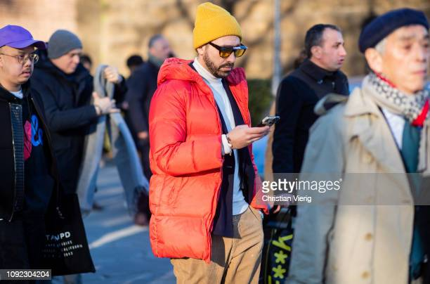 A guest is seen wearing yellow beanie red down feather jacket during the 95th Pitti Uomo at Fortezza Da Basso on January 10 2019 in Florence Italy