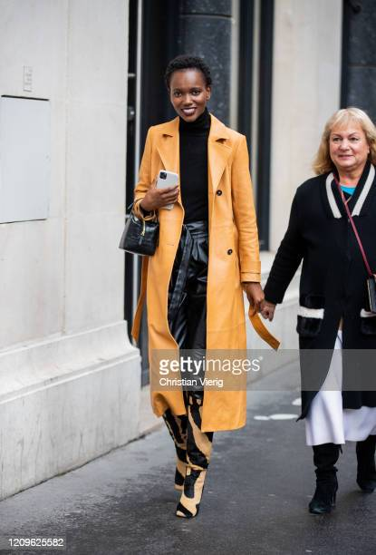 A guest is seen wearing yellow coat Khaite boots outside Ralph Russo during Paris Fashion Week Womenswear Fall/Winter 2020/2021 Day Five on February...