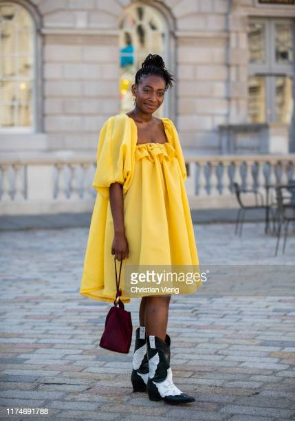 A guest is seen wearing yellow dress cowboy boots red velvet bag outside Fyodor Golan during London Fashion Week September 2019 on September 14 2019...