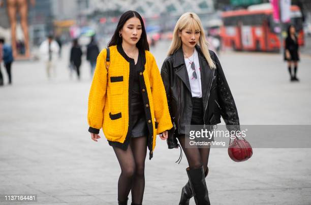 A guest is seen wearing yellow jacket black mini skit and a guest wearing black Gucci leather jacket red bag sheer tights black boots at the Hera...