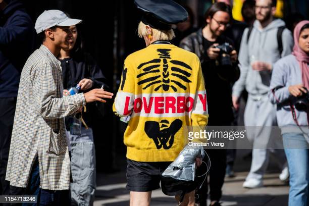 Guest is seen wearing yellow knit with print loverboy outside John Lawrence Sullivan during London Fashion Week Men's June 2019 on June 08, 2019 in...