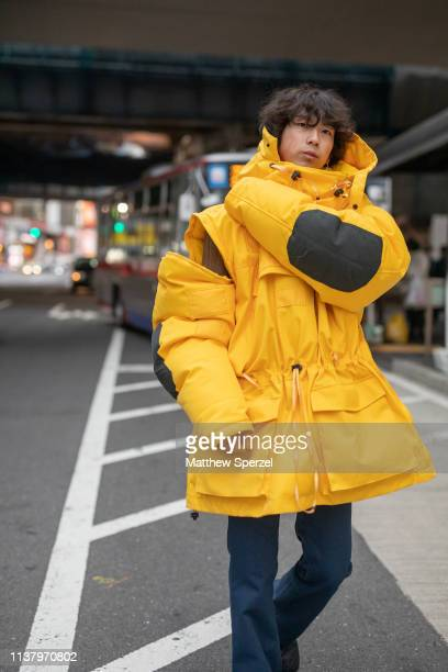 A guest is seen wearing yellow ski jacket navy pants during the Amazon Fashion Week TOKYO 2019 A/W on March 23 2019 in Tokyo Japan