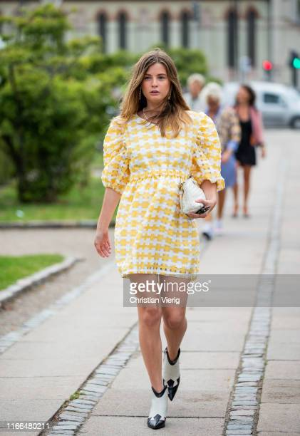 Guest is seen wearing yellow white dress, white clutch outside Blanche during Copenhagen Fashion Week Spring/Summer 2020 on August 06, 2019 in...