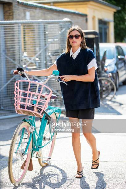 Guest is seen with a bike outside Samsøe & Samsøe during Copenhagen Fashion Week Spring/Summer 2021 on August 11, 2020 in Copenhagen, Denmark.