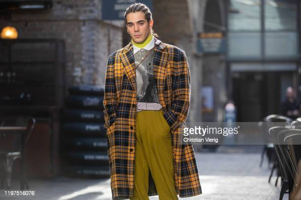 A guest is seen with braids wearing yellow blue checked coat yellow pants shirt with graphic print outside Jordan Luca during London Fashion Week...