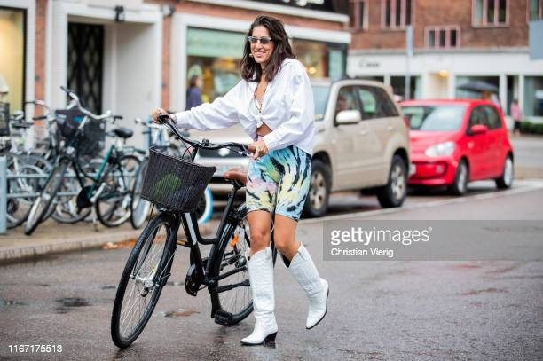 A guest is seen with her bike wearing cycle pants white button shirt white cowboy boots outside Saks Potts during Copenhagen Fashion Week...