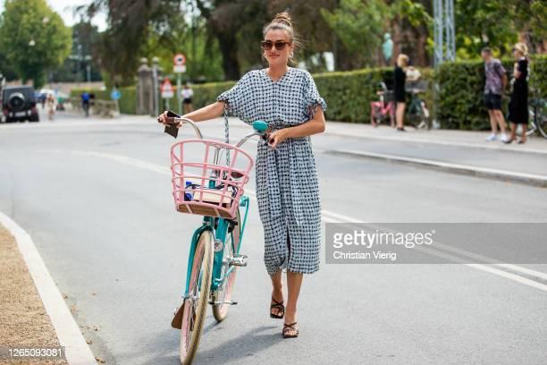 Guest is seen with her bike wearing white dress outside 7 days active during Copenhagen Fashion Week SS21 on August 10, 2020 in Copenhagen, Denmark.