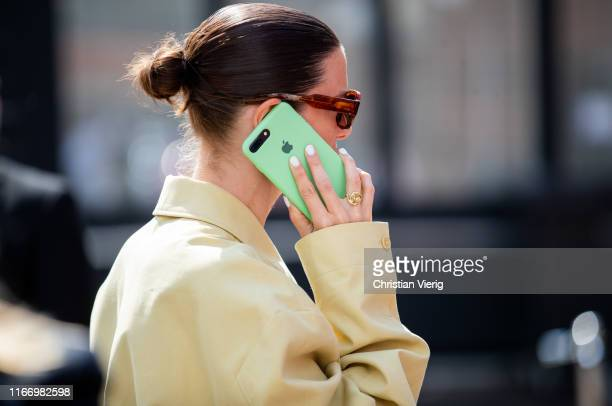 Guest is seen with her green Iphone outside By Malene Birger during Copenhagen Fashion Week Spring/Summer 2020 on August 08, 2019 in Copenhagen,...