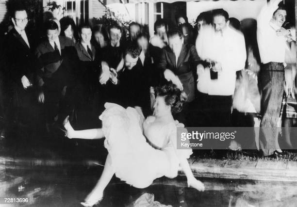 A guest is thrown fullyclothed into the swimming pool at a party given by French photographer Louis Dalmas during the International Film Festival at...