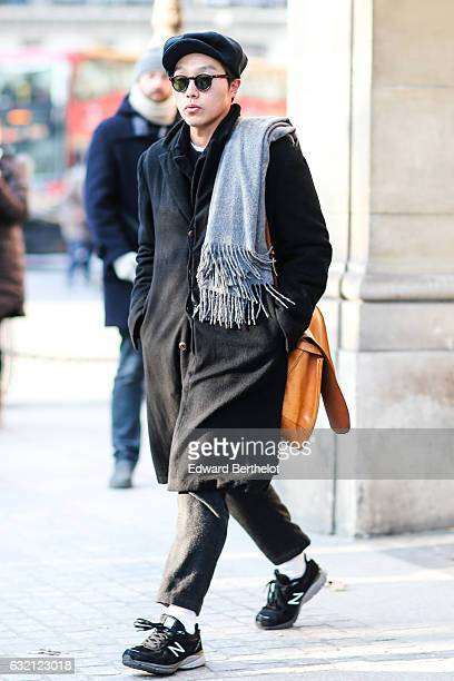 A guest is wearing a beret hat an orange leather bag a black long coat and a scarf after the Louis Vuitton show during Paris Fashion Week Menswear...