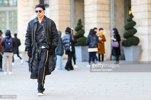A guest is wearing a black beanie hat black sunglasses a black long coat a black kimono black sportswear pants and white sneakers after the...