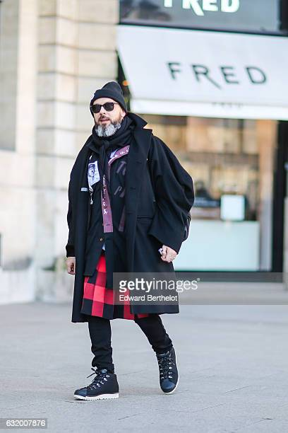 A guest is wearing a black beanie hat black sunglasses a black scarf a red and black checked skirt black pants and black shoes after the Balenciaga...