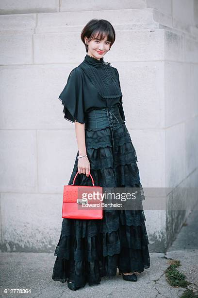 A guest is wearing a black dress and a red bag outside the Shiatzy Chen show during Paris Fashion Week Spring Summer 2017 at Grand Palais on October...