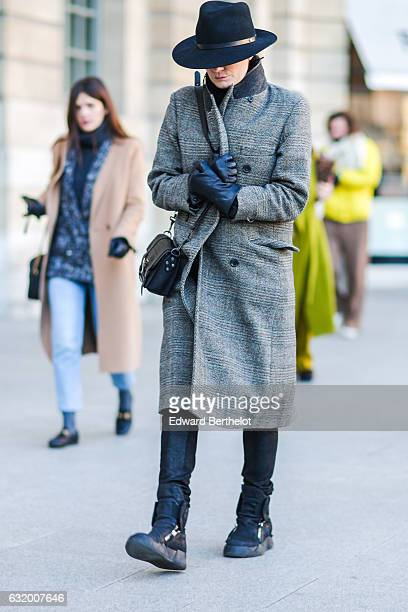 A guest is wearing a black hat a gray long coat a black bag black pants and black boots after the Balenciaga show during Paris Fashion Week Menswear...