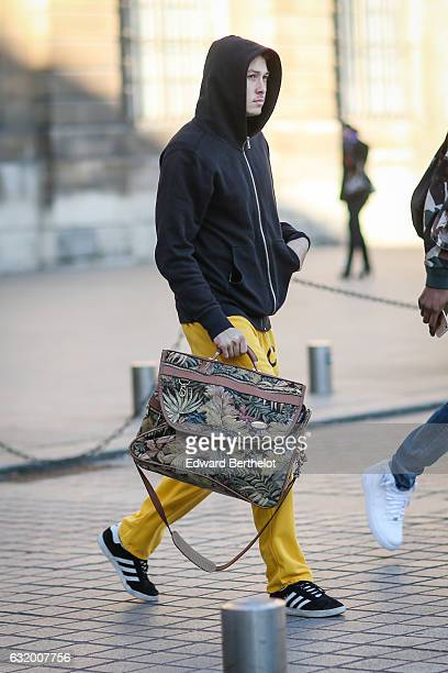 A guest is wearing a black hoodie top yellow pants Adidas black shoes and a flow print bag after the Balenciaga show during Paris Fashion Week...