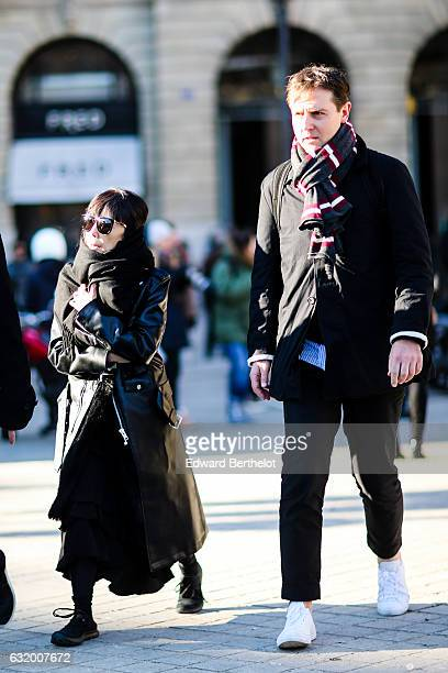 A guest is wearing a black scarf a black leather jacket sunglasses and black boots after the Balenciaga show during Paris Fashion Week Menswear...
