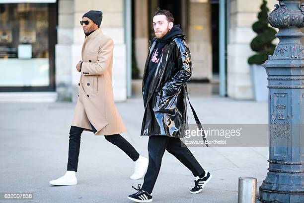 A guest is wearing a black shiny long coat a black hoodie with a pink print black pants and black shoes after the Balenciaga show while another guest...