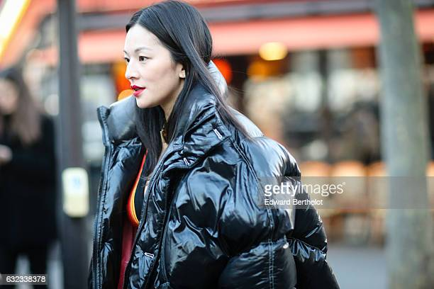 A guest is wearing a black shiny oversized winter coat and thigh high black boots outside the Balmain show during Paris Fashion Week Menswear...