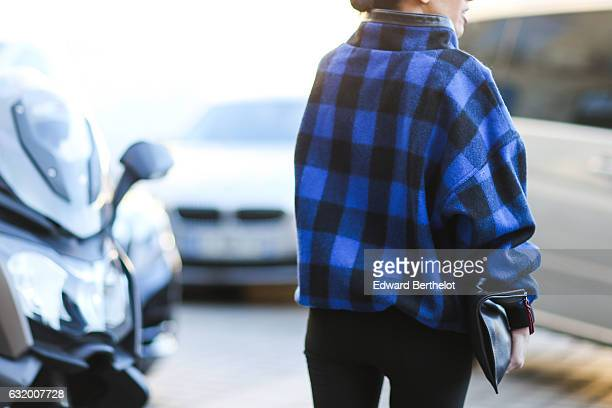 A guest is wearing a blue and black checked coat sunglasses black pants a black bag and black leather thigh high boots after the Balenciaga show...