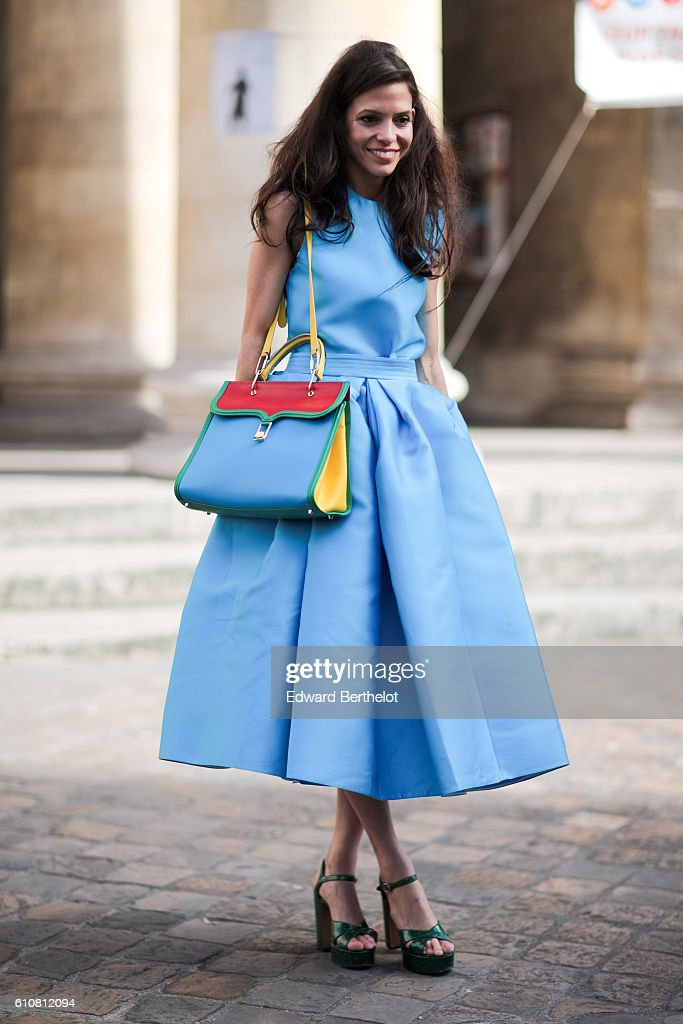A guest is wearing a blue dress and a blue bag outside the Nehera show on September 27, 2016 in Paris, France.
