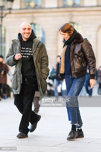 A guest is wearing a brown leather bomber jacket a dark blue top a black scarf blue denim jeans pants black shoes and is smoking after the Balenciaga...