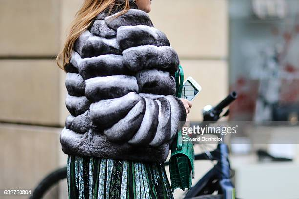 A guest is wearing a gray puffer coat and a green Hermes crocodile leather bag outside the Elie Saab show during Paris Fashion Week Haute Couture...