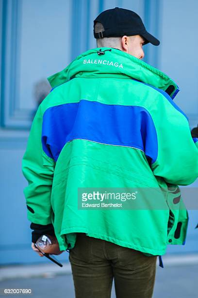 A guest is wearing a green and blue Balenciaga coat and a black cap after the Balenciaga show during Paris Fashion Week Menswear Fall/Winter...