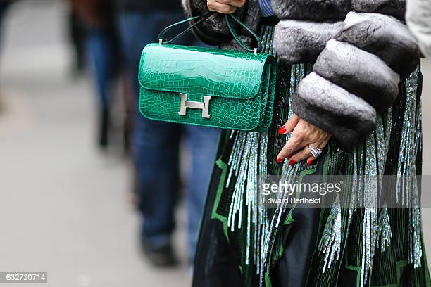 A guest is wearing a green Hermes crocodile leather bag outside the Elie Saab show during Paris Fashion Week Haute Couture Spring Summer 2017 on...