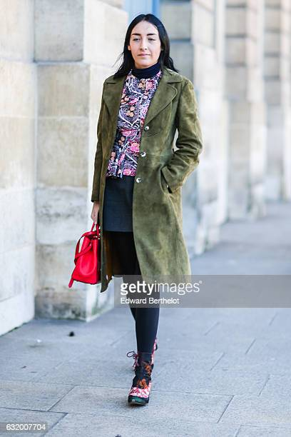 A guest is wearing a green long coat a flower print top a black leather skirt black tights and a red bag after the Balenciaga show during Paris...