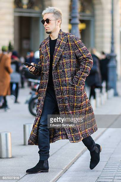 A guest is wearing a long coat black pants black shoes and sunglasses after the Balenciaga show during Paris Fashion Week Menswear Fall/Winter...