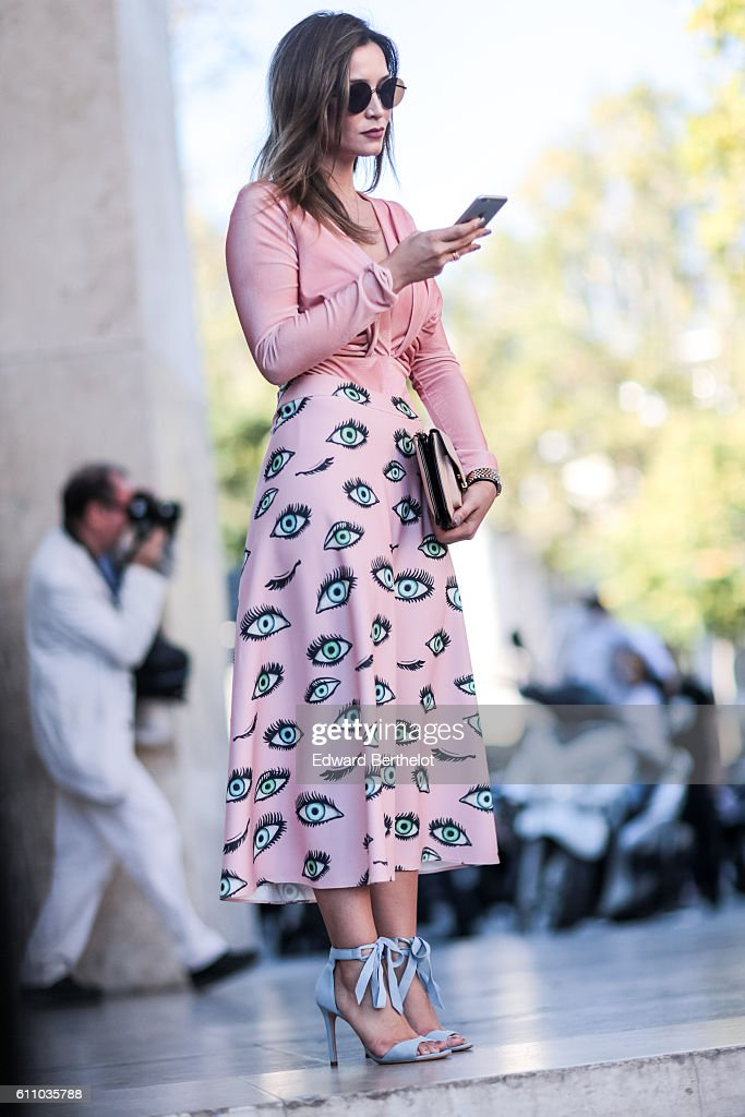 A guest is wearing a pink top, a pink skirt with eyes drawn on it, sunglasses, and blue shoes, outside the Rochas show, at the Palais de Tokyo, during Paris Fashion Week Spring Summer 2017, on September 28, 2016 in Paris, France.