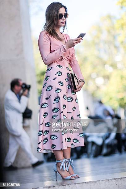 A guest is wearing a pink top a pink skirt with eyes drawn on it sunglasses and blue shoes outside the Rochas show at the Palais de Tokyo during...