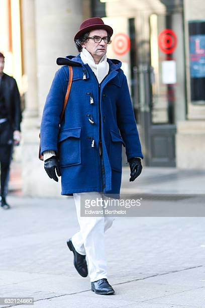 Guest is wearing a purple hat, a blue long coat, glasses, white pants, gloves, a brown leather bag, and black shoes, after the Louis Vuitton show,...