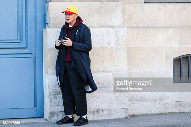 A guest is wearing a red and yellow cap a dark blue long coat a red hoodie top black large pants and black shoes after the Balenciaga show during...