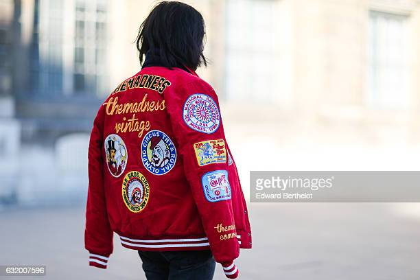 A guest is wearing a red coat with the inscription The Madness Vintage after the Balenciaga show during Paris Fashion Week Menswear Fall/Winter...