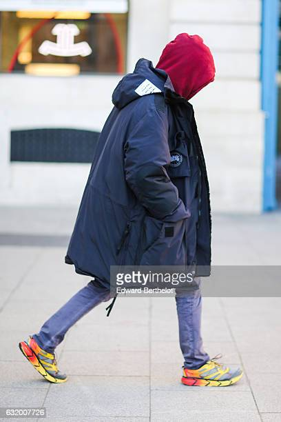 A guest is wearing a red hoodie a blue long winter coat purple pants and yellow shoes after the Balenciaga show during Paris Fashion Week Menswear...