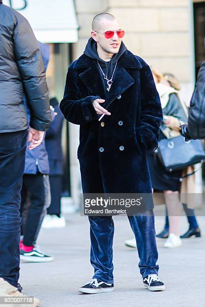 A guest is wearing a red sunglasses a blue long coat a black hoodie a long necklace blue pants and sneakers shoes after the Balenciaga show during...