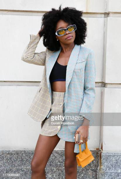A guest is wearing a suit with a handbag during New York Fashion Week at Spring Studios on September 07 2019 in New York City
